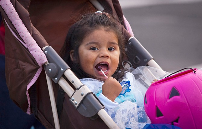 Jaslene Valencia, 2, enjoys a candy as she is wheeled to The Dalles Chronicle office, one of many businesses particpating in the downtown Trick-or-Treat.