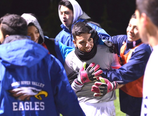 HRV goalieMarco Cuevas is mauled by his teammates at halftime of Tuesday's state semifinal game between the Hood River Valley Eagles and the Wilsonville Wildcats. Cuevas made a key save on a penalty kick to keep Wilsonville scoreless.