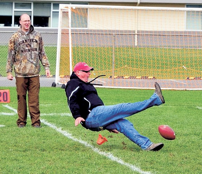 """Sunnyside Christian High School supporter Mike Duim ended up on the ground during Bleyhl's """"Kick for Cash"""" campaign."""