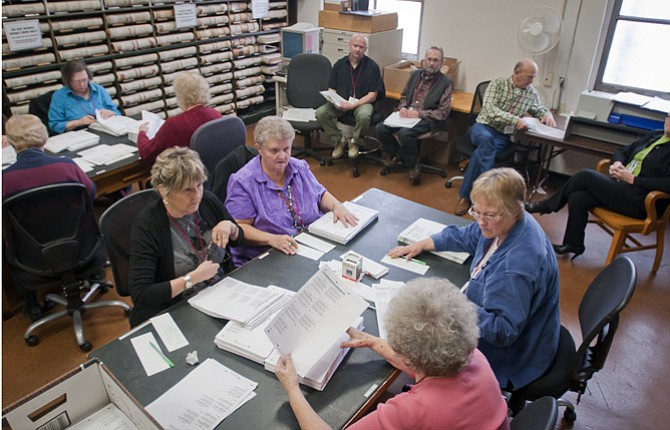 VOTES ARE re-counted by hand in the back room of the County Clerk's office under the careful eye of observers sitting against the wall. Pictured at the foreground table are, left to right, facing the camera, Janet Sedey and Susan Conley. Seated across from them are, left to right, Jan Simer and Donna Lindsey. They represent a mix of political parties with two Republicans, one Democrat and an Independent.