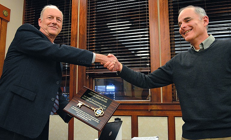 Outgoing Mayor Arthur Babitz (right) accepts a plaque adorned with a key to the city from City Manager Steve Wheeler at the conclusion of Monday night's Hood River City Council meeting.