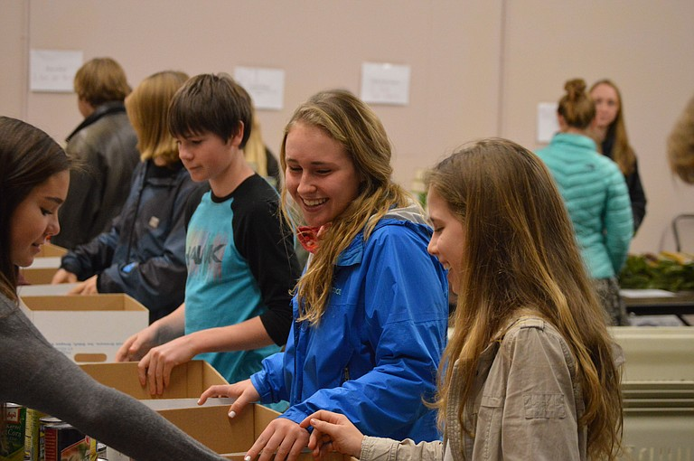 Students laugh as they load boxes at Hood River Armory Thursday for Hood River County Christmas Project. At center are freshmen Thomas Mixon and Abbie Bergemann.