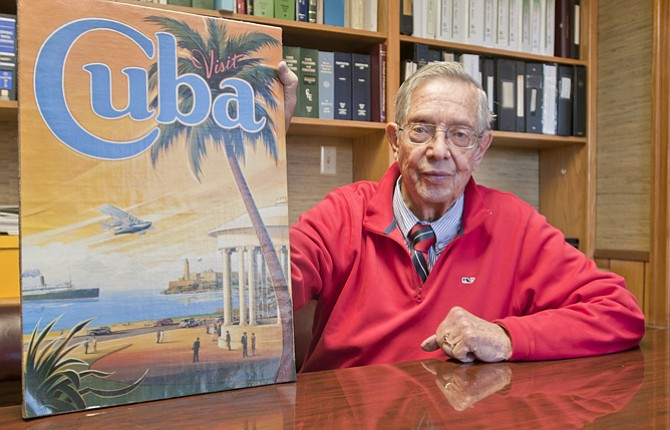 M.D. Van ValkenBurgh sits with a poster from Cuba, where he visited in 1997. He is glad to see relations changing for the better between America and Cuba, which is the same distance from the Florida coast as The Dalles is from Portland.