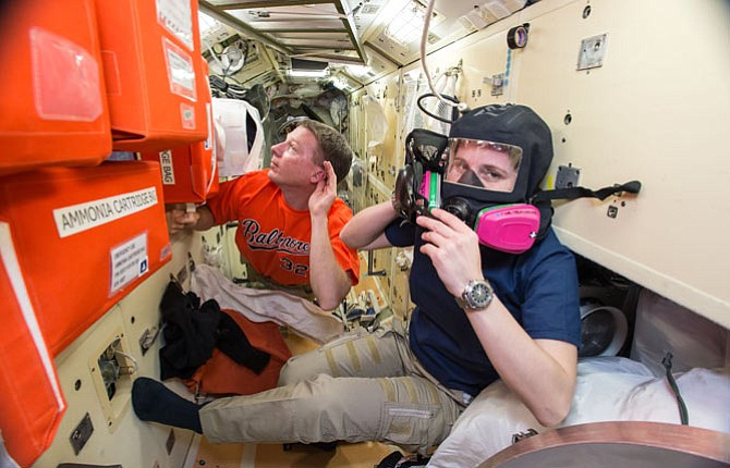 In this image provided by NASA taken during a training exercise, U.S. astronaut Terry Virts, left, assists European Space Agency astronaut Samantha Cristoforetti with emergency training aboard the International Space Station. Astronauts evacuated the U.S. section of the International Space Station and moved to its Russian module after a problem emerged Jan. 14.