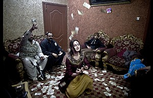 Pakistani Waseem Akram, 27, dances during a private party in Rawalpindi, Pakistan, Jan. 15. By day, Akram sells mobile phone accessories from an alleyway shop in an old neighborhood of this Pakistani city. But by night he becomes Rani, a female wedding party dancer.