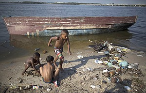 boys play next to an abandoned boat, on the garbage-littered shore of Guanabara Bay in Rio de Janeiro, Brazil, Jan. 20. Rio de Janeiro state's top environmental official acknowledged that the Olympic pledge of slashing by 80 percent the levels of pollution flowing into the trash- and raw sewage-filled Guanabara Bay is unattainable by next year's summer games.