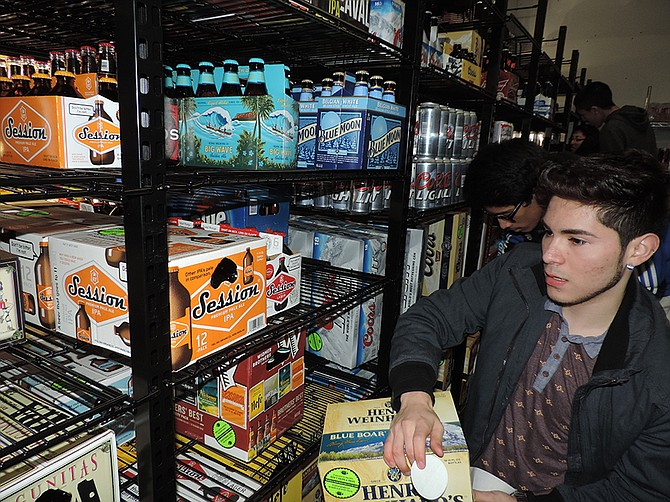"""SENIOR Sam Ortiz of Health Media Club applies """"Don't Drink and Drive"""" stickers to beer in the """"beer cave"""" at Windmaster Market on Thursday."""