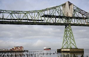 a freighter is visible under the Astoria-Megler bridge in Astoria Oct. 15. Ships drop more than just their anchors when they settle into the Astoria Anchorage, giving the economy a boost as crews hit dry land for supplies.