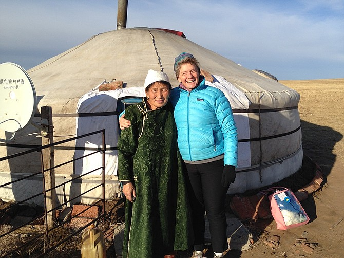 """""""It is a vast, beautiful landscape,"""" writes Jan Brauer, top, with the mother of a translator, outside her yurt home, which is warmed by a cattle dung-burning stove. It has two beds, a table and a TV."""