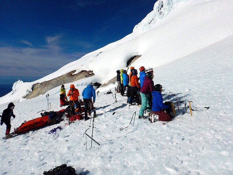 Mountain rescue: Volunteers form a protective line to stop falling ice from hitting an injured climber on the south side of Mount Hood last Saturday.