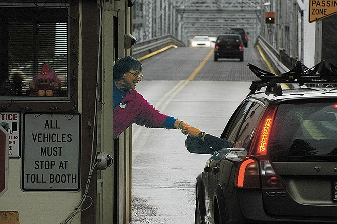 BRIDGE of the Gods toll employee Peggy Towery reaches to accept a toll from a driver heading north. Port officials are looking at creating an electronic toll system for the first time in the bridge's 90-year history.