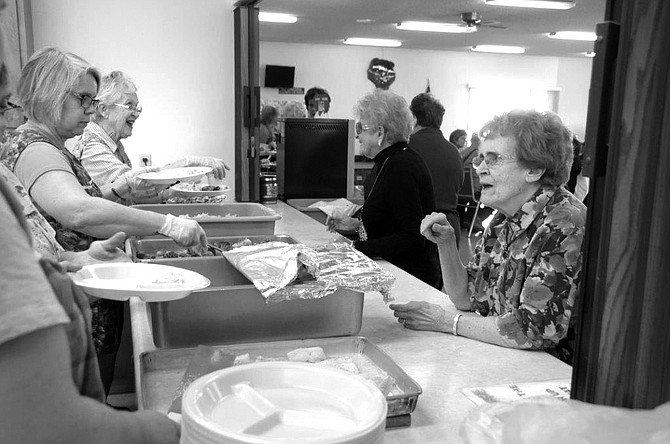 Grangeville Senior Citizens meal participants, Ruth Amstutz and Lucy Loeber, are greeted by meal servers Feb. 13.