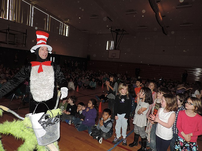 BILL 'Cat in the Hat' Newton parks his green bicycle in the Westside gym, to the childrens' delight, at Friday's kickoff assembly for Read Across America.