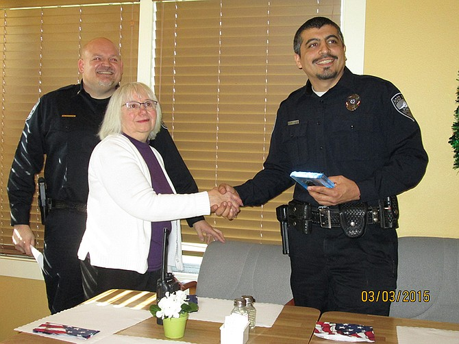 AUXILIARY president Judy Osbourn gives the award to Officer Juan Pulido. At left is Chief Neal Holste.