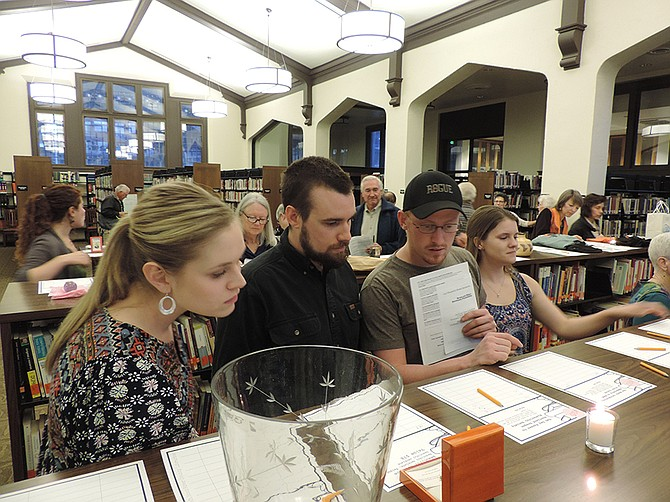 Feast of Words fundraiser attendees peruse varied silent auction items Saturday among the stacks in the Library's historic reading room. The event surpassed the $25,000 goal.