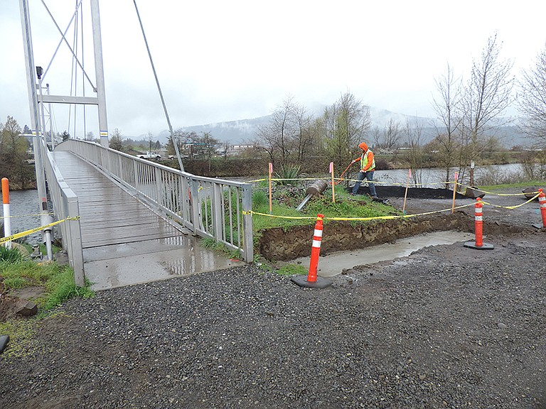 A PROJECT inspector takes measurements Monday at the east end of the footbridge over the Hood River.