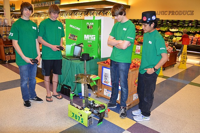 Members of HRVHS robotics team Men in Green, Luke Serra, Joey Slover, Michael McAllister and Ruben Gonzaga show off their robot, Roberta, at Rosauers Friday. The robotics team was funded by the School Aid program which donates proceeds from Mt. Hood Organic Farms fruit in a bin at Rosauers through spring and summer every year.