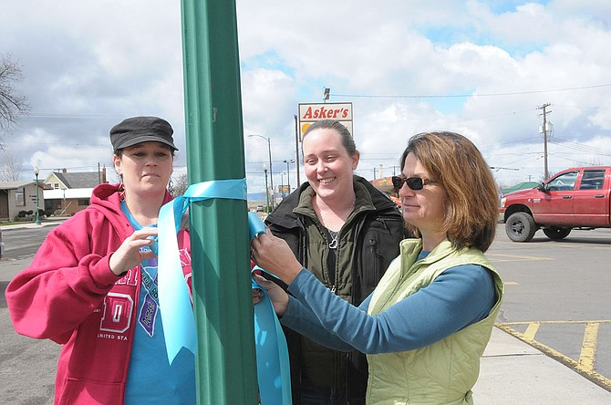 (L-R) YWCA advocate Kristy Beckstead and area task force volunteers Amanda Davis and Marsha Lance were busy hanging teal Sexual Assault/Domestic Violence Month Awareness ribbons on Grangeville's Main Street Thursday, April 3.