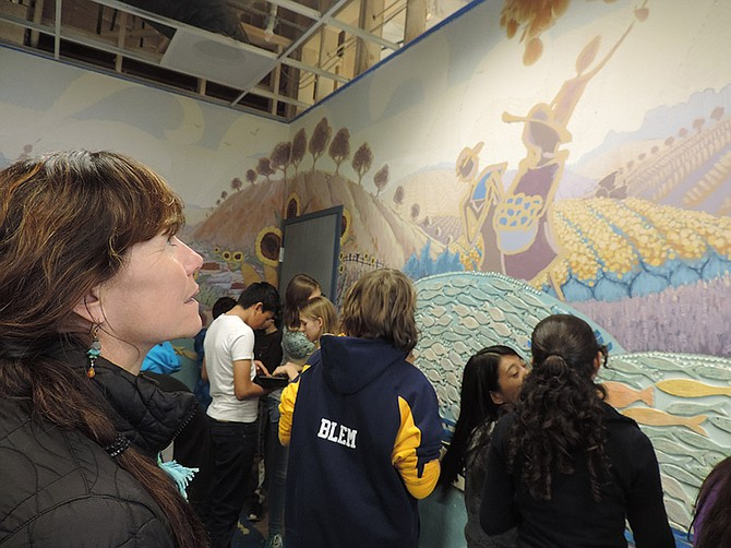TEACHER Jennifer Wilson, above, looks on as students add glass beads around figures on the FISH food bank mural.