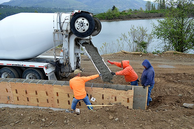 PORT CREWS from Peterson Bros. Construction pour a concrete retaining wall Thursday afternoon at the northern end of the Nichols Basin on the Hood River waterfront, part of the Port's Nichols Basin West Edge trail project. The Port also started pouring concrete for a sidewalk portion of the trail on Monday.