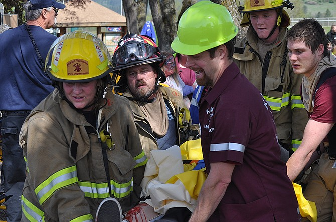 Firefighters and EMTs carry a patient to a waiting ambulance for transport during Saturday's mass casualty exercise in Kamiah. Multiple regional EMS agencies participated in the April 25 training to build on skills and practice interagency cooperation.