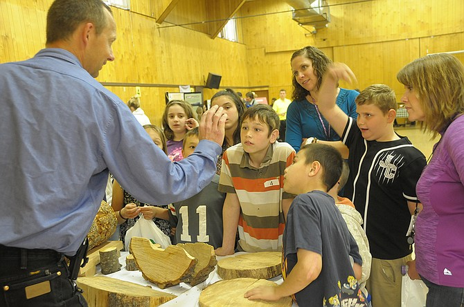 The annual Farm and Forestry Fair in Greencreek welcomed fourth and fifth graders to the community hall to learn about a variety of farm and forest products. Here, Glenn Poxleitner shows students a ring cut from a tree.
