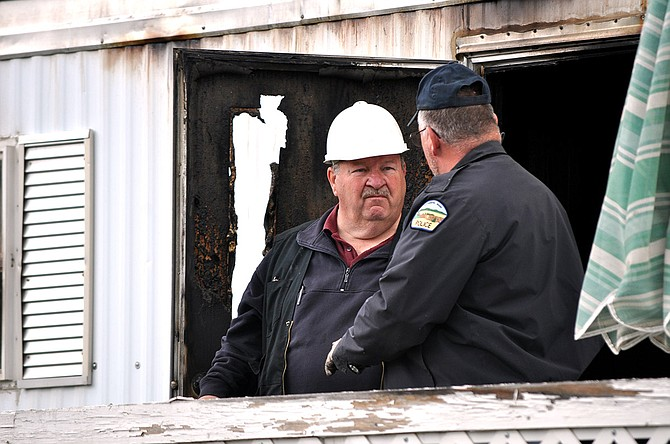 State Deputy Fire Marshal Bill Steele points to charred trailer home remains last Wednesday, May 13, during an investigative walk through with CPD Chief Terry Cochran (not pictured).