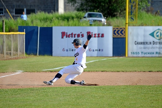RILEY VAN HOOSE slides into third base during Friday's game against The Dalles. Van Hoose had a two-run single and scored a run himself to help HRV get a victory over the Riverhawks.