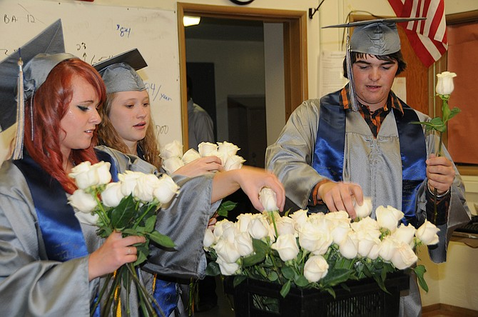 Grangeville High School seniors (L-R) Taylor Wilkins, Kristin Kaschmitter and Lonnie Barreiros choose the roses they give to family and friends during the May 22 ceremony. Upcoming graduations include Prairie May 29, Highland May 30, and Summit Academy June 6.