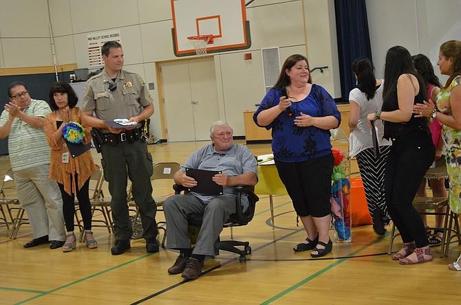 PRINCIPAL Dennis McCauley receives an award from Kim Yasui at Mid Valley Elementary school Thursday night as Hood River County Sheriff Matt English, left, looks on.