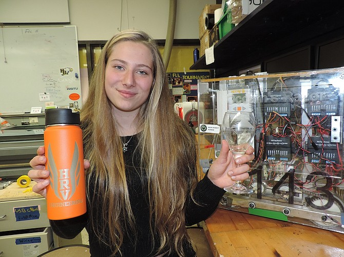 Robotics student Victoria Kohner-Flanahan displays laser-etched items created by Engineering students; at right is a student-built robot.