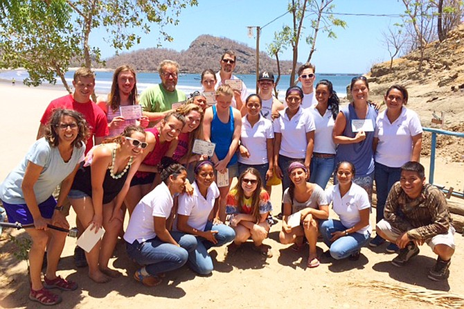 The team of 12 students and six chaperones poses on the beach.