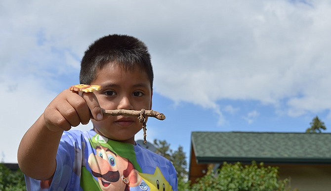 Jose Rueda, a kindergartner at Mid Valley Elementary School, shows off a dead worm he found while weeding in the school garden plot.