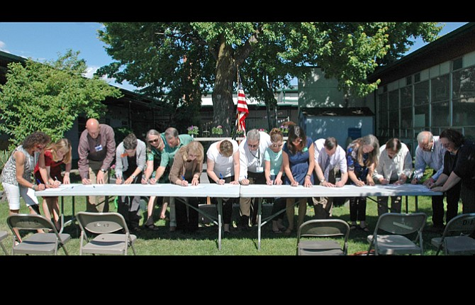 REPRESENTATIVES FROM a host of public, nonprofit and private organizations sign individual pledges committing to an effort to reduce childhood obesity in Wasco County during a ceremony in the school garden at Chenowith Elementary.