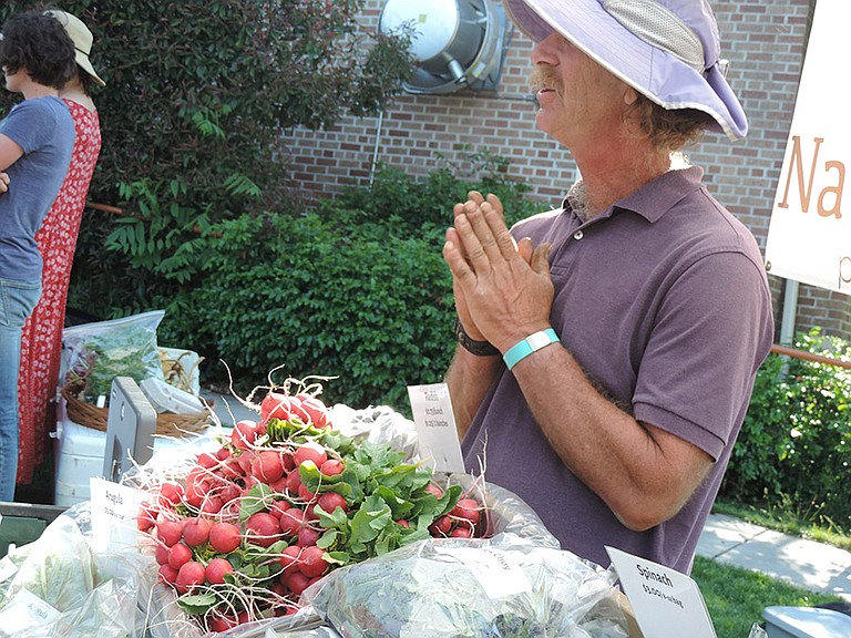 Parkdale farmer Ronny Tannenbaum seems to be providing a greeting and gesture of blessing as he talks with clients about radishes he grew at his Nature's Finest farm, and sells at Gorge Grown Farmers Market.