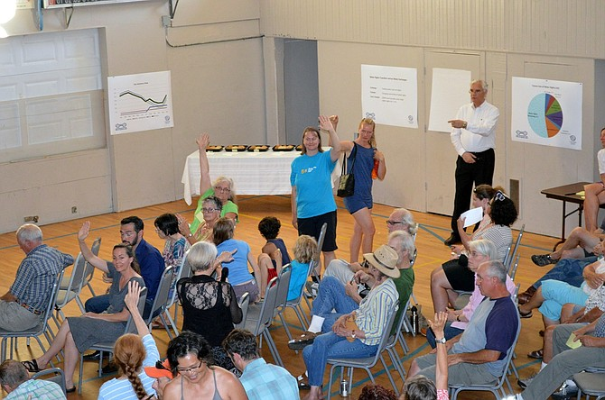 NESTLE TOWN HALL brings in more than 120 people at the Cascade Locks City Hall last Thursday night. Audience members raise their hands for a chance to speak. Gordon Zimmerman, Cascade Locks City Administrator, points to the next speaker.
