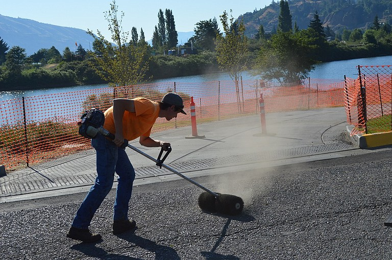 DUST FLIES from a power brush as Brandon Brockel of Seal Kote, based in The Dalles, cleans dirt and gravel from the street neighboring Nichols Basin Trail. The paved trail opens to pedestrians today.