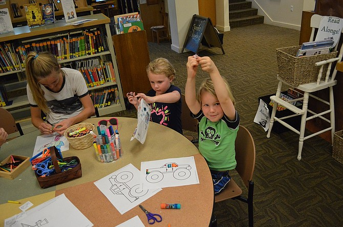 "Coloring time proves exciting at the Hood River County Library's Crafternoon last week. Jamie Robinson, 14, leads the session with Ivar Van Rutledge, 4, and Savina Davis, 4. Also at the table was Savine's sister, Olympia Davis, 7. ""When I grow up, I want to be a pirate,"" mused Savine as she worked."