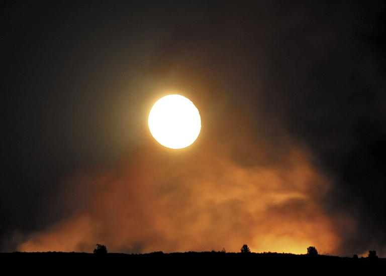 A full moon shines through the smoke of a wildfire that ignited late Friday along state Highway 155, near Rondeau Road, about 5 miles south of Omak.