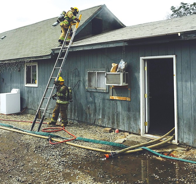 Firefighters with Yakima County Fire District #5 douse a grease fire that extended into the attic of a triplex in Outlook.