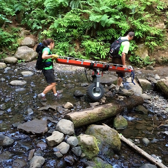 "CRAG RATS roll a gurney through a stream in the Eagle Creek area of western Hood River County, en route to a medical rescue call in late June. The Crag Rats are being assisted by a combined ""Reach and Treat"" program this year which boosts their numbers and speeds up response times."