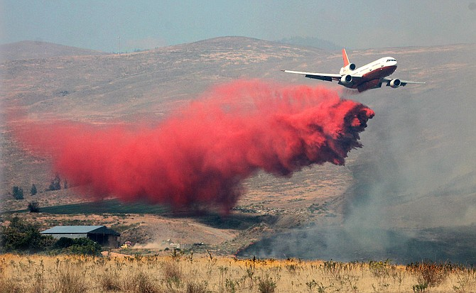 An aircraft flies low over the Scotch Creek area near Conconully dropping fire retardant on the dry grass and sagebrush.