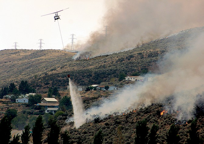 A helicopter drops water on the burning hillside above Riverside earlier today.