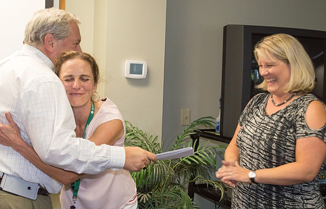 DR. JUDY Richardson, representing Girl Scout Troop 50202, is given a celebratory hug by Mid-Columbia Medical Center President/CEO Duane Francis as Sonja Little looks on. The Girl Scouts were among the recipients of charitable contributions from MCMC earlier this month that were based on the amount of hours that employees volunteered in their communities. Richardson is a family practice physician at Columbia Crest Family Medicine.  	Contributed photo