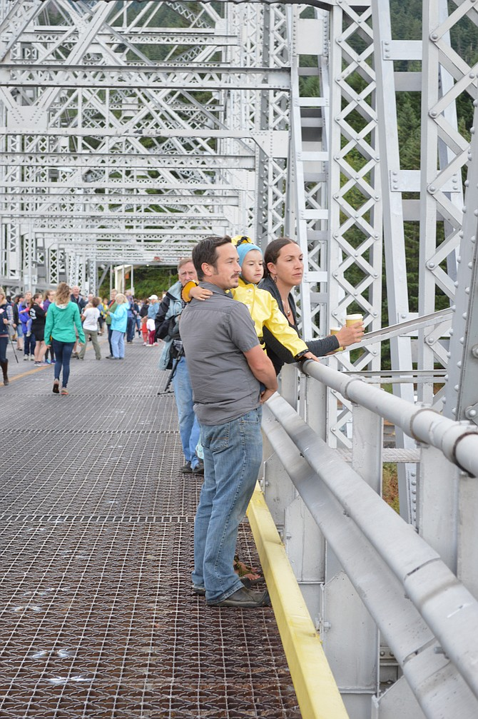 Views from the Bridge: Gabriel and Samantha Namay of Portland take a moment to look out over the Columbia River with their 4-year-old daughter, Ronin, as they walk across the Bridge of the Gods in the annual community walk over the scenic bridge on Saturday. Pedestrian access is available at any time, for 50 cents, and walkers must carefully traverse it along with vehicles. For the annual walk, the bridge is closed to vehicles, allowing people to stroll, walk, or bike over the bridge, and to stop awhile to peer over the edge and admire the views of Oregon and Washington.