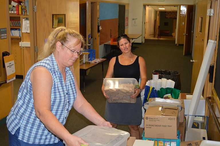 Mid Valley Elementary teacher Denise Long helps new kindergarten teacher Diana Robertson sort classroom supplies in the school's hallway Aug. 29. Long has been at Mid Valley since 2004, and has taught kindergarten for the past five. Robertson is one of nine new teachers at Mid Valley.