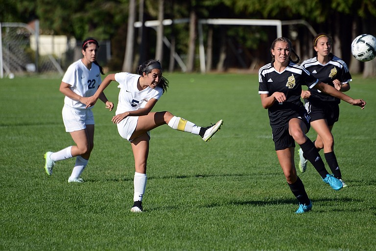 Junior midfielder Cielo Rivera delivers a kick past two St. Helens defenders.