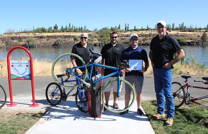 CH2M HILL Project Manager Richard Wolf, from left, Northern Wasco County Parks and Recreation Executive Director Phil Lewis and Recreation Coordinator Danny Kittleson as well as CH2M Operating Engineer Mitch Riefel show off the new Bike Fixtation Station at Riverfront Trail in The Dalles.