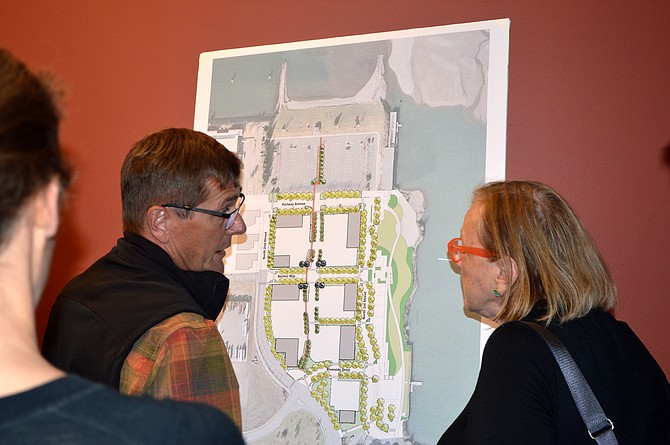 Port commissioner Rich McBride and city planner Cindy Walbridge discuss a proposed Lot 1 design by Walker Macy consulting firm at an open house Tuesday evening. The plan lays out how sections of the 7.5-acre waterfront property will be used for combined light industrial, parking and pedestrian access. The red line at center is a pedestrian pathway cutting north through the entire parcel.