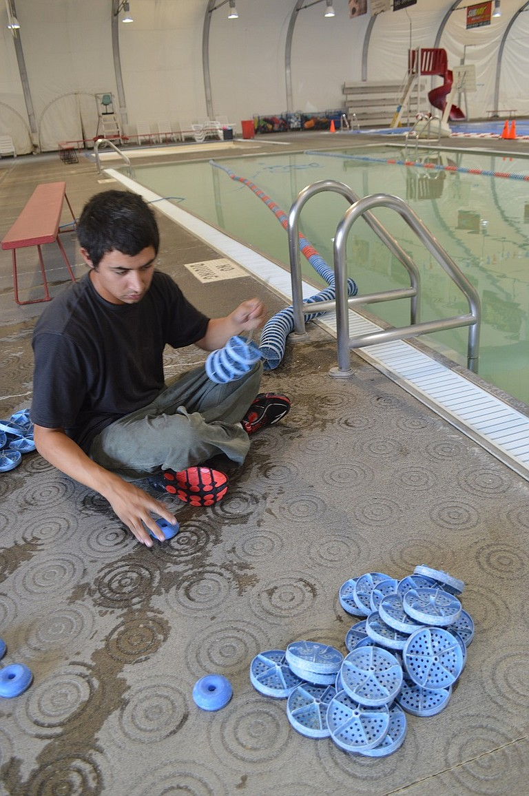 Pool employee Brandon Sanchez strings together reused lane dividers for the therapy pool, as part of this week's closure for maintenance at Hood River Aquatic Center. The lane markers will assist in program flexibility for the pool's varied uses for play and for exercise.